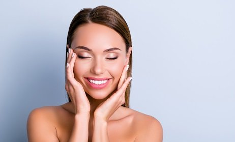 Portrait of pleased satisfied girl touching face enjoying ideal perfect skin after procedure mask keeping eyes closed isolated on grey background
